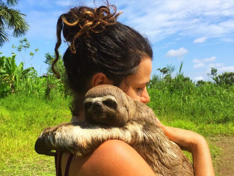 Girl holding sloth monkey in Peruvian Amazon during the day.