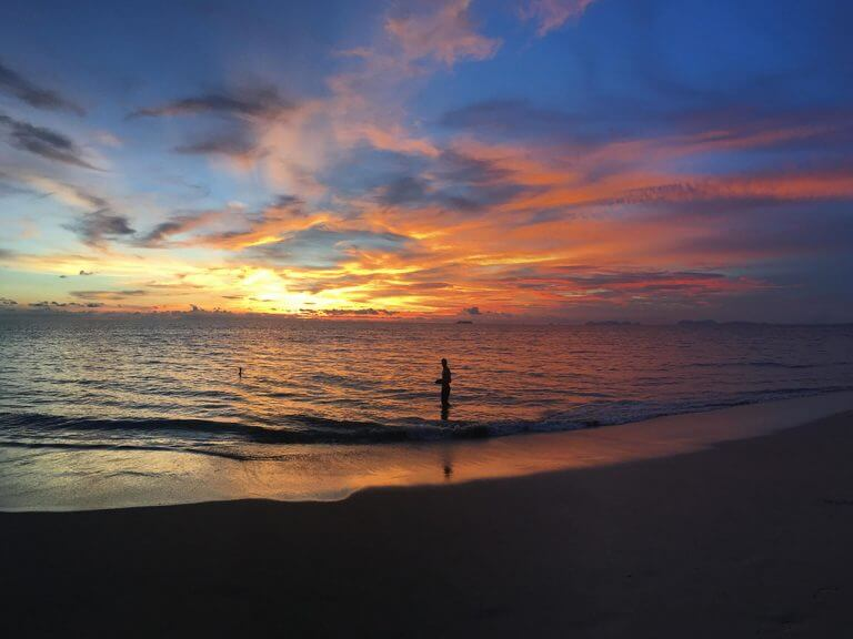 Man standing in ocean in Kolanta Island in Thailand. Sun is setting. Sky is multicolored: blue, orange, red and yellow.