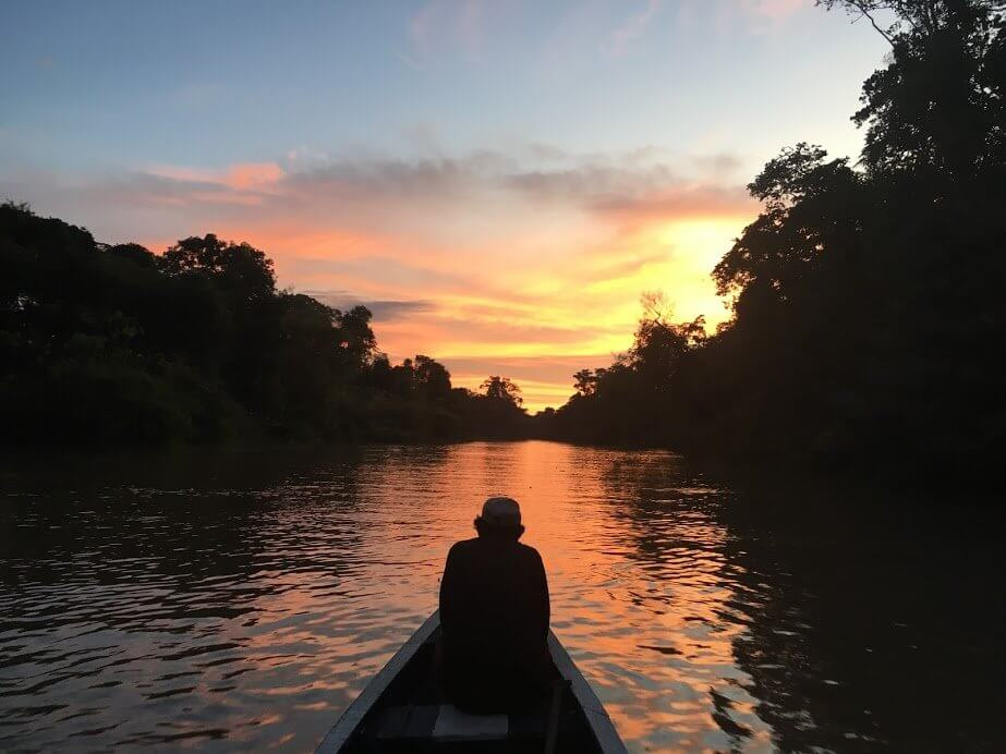 Man on a boat while floating down the Peruvian Amazon River while the sun is setting. Sky is blue, orange, yellow and red. The man is on an adventure in the Peruvian amazon.