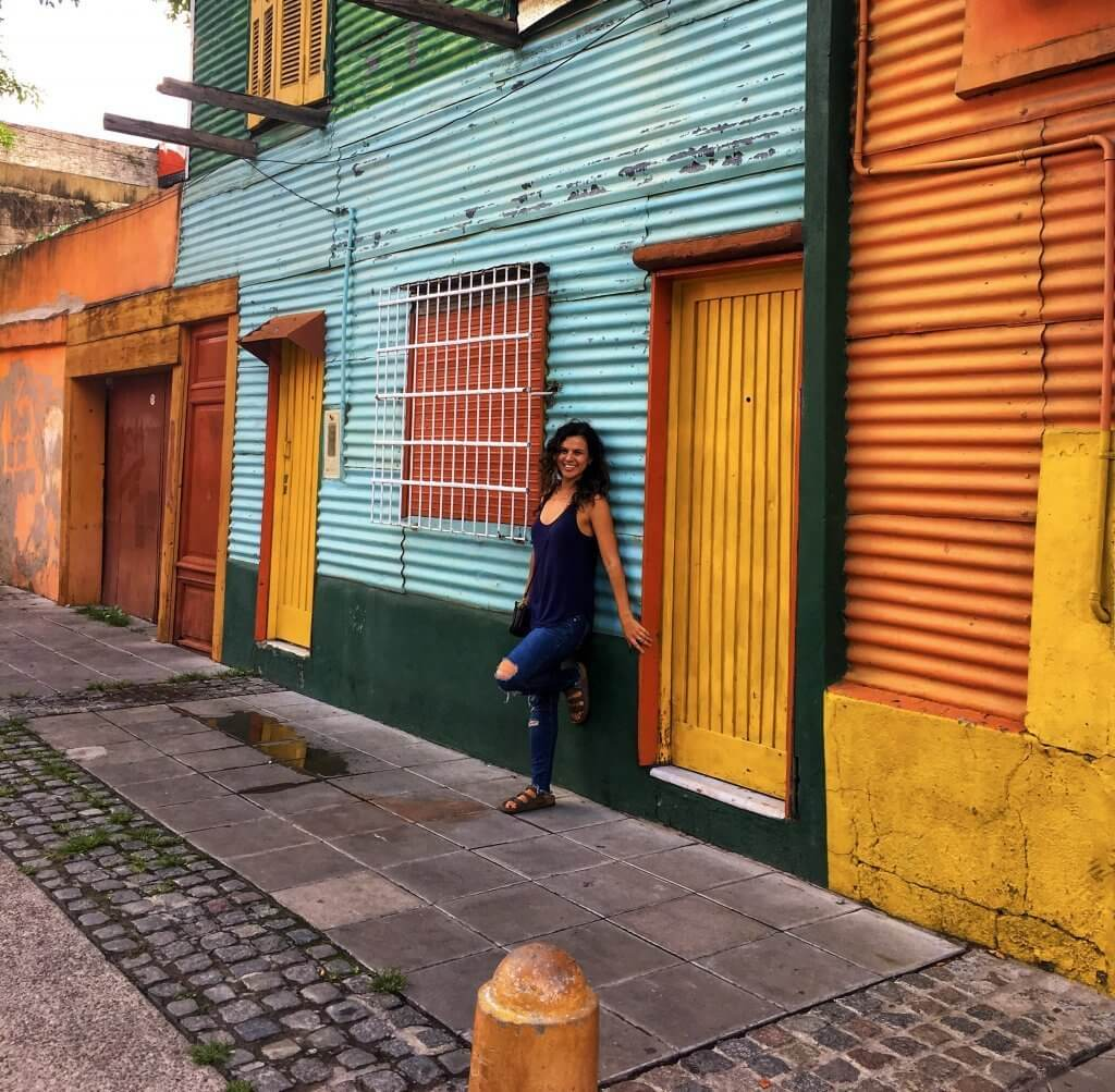Picture of girl who wrote Argentina travel guide. Girl is in Buenos Aires in front of a colored house in the La Boca district of Buenos Aires.