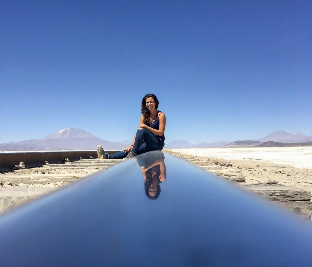 Girl who wrote Bolivia Travel Guide is sitting on a train track in Salar de Uyuni Bolivia. The girls image is reflected on the train track and mountains and desert are in the background.