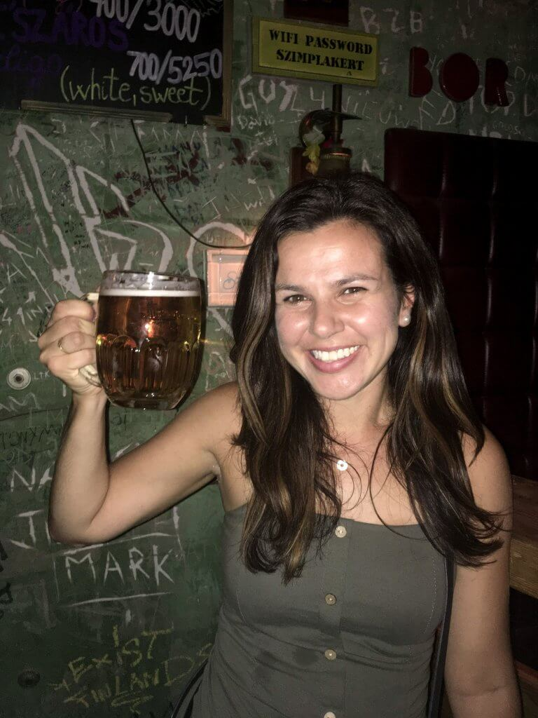 Picture of girl who wrote Hungary travel guide. Girl is holding a pint of beer in a bar in Budapest Hungary.