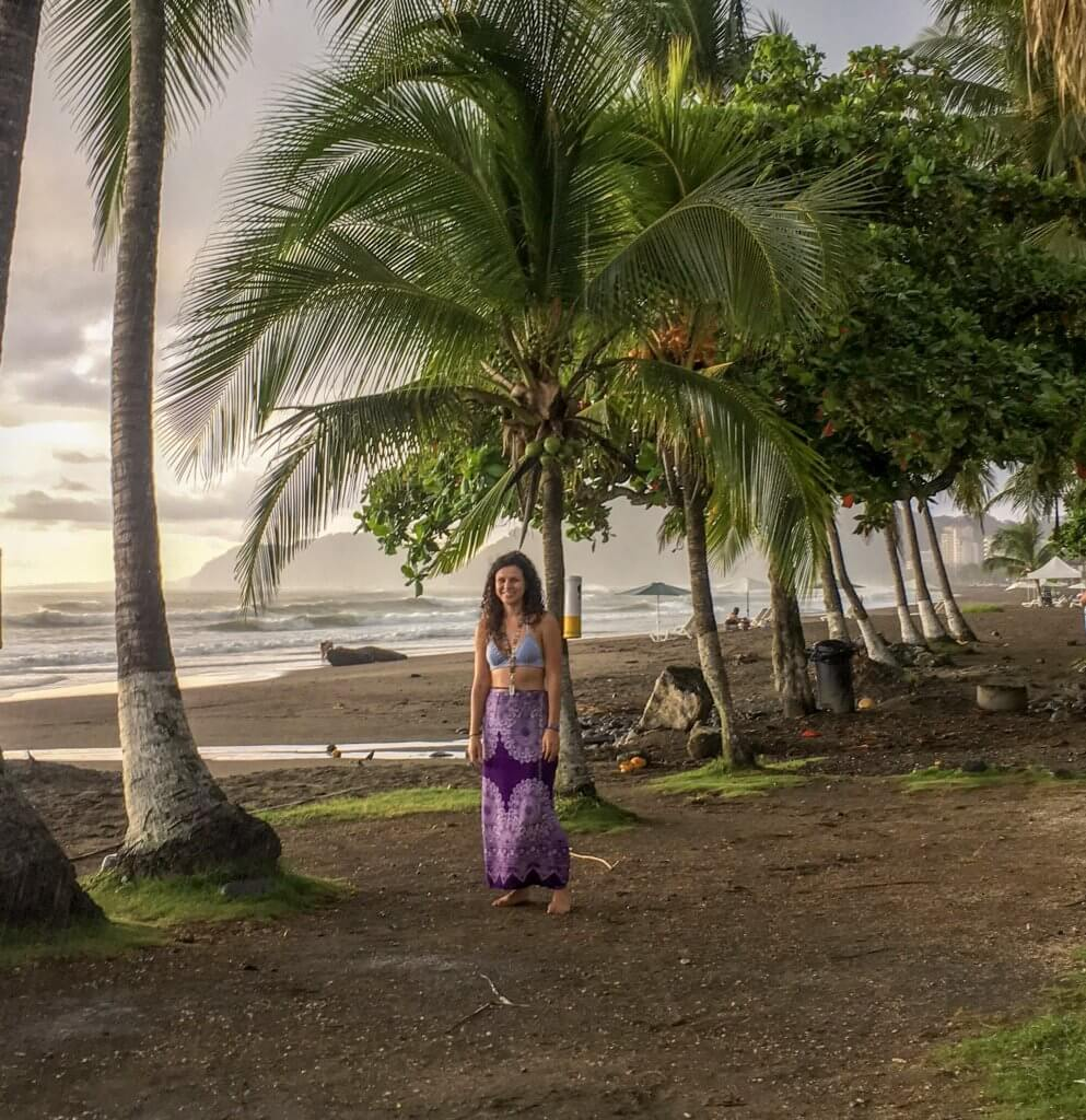 Picture of girl who wrote Costa Rica Travel Guide. Girl is on Jaco Beach in Costa Rica wearing a sarong. Ocean is shown in the background. Palm trees are blowing in the wind.