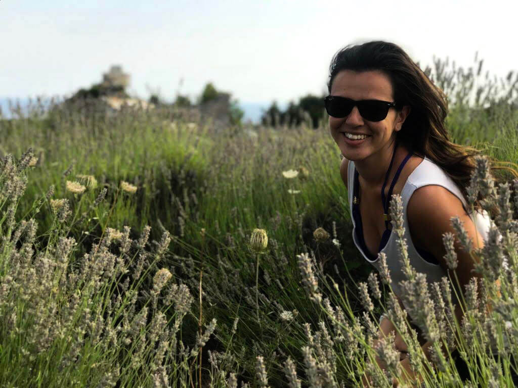 Girl who wrote Croatia Travel Guide. Girl is in a lavender field in Croatia. Girl is wearing sunglasses and smiling inside field.