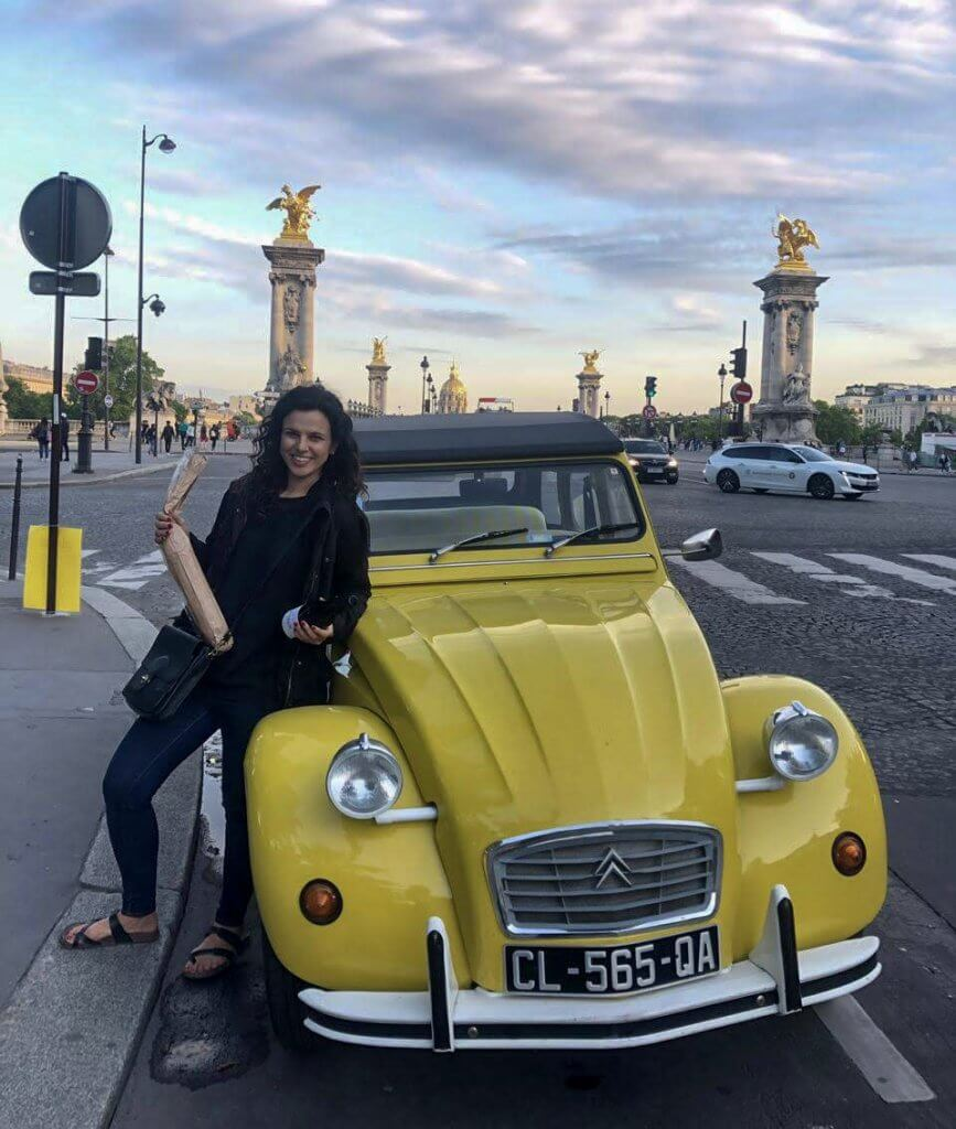 Girl who wrote France Travel Guide is standing in front of an old Yellow car in Paris and holding a baguette.