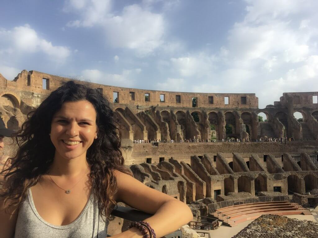 Girl who wrote Italy travel guide. Girl is standing in front of the Coliseum in Rome Italy.