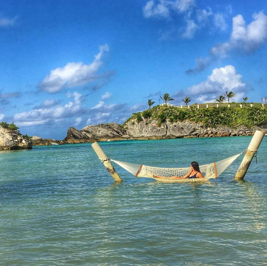 Girl who wrote the Bermuda Travel Guide laying down on a hammock in the middle of the ocean in Bermuda. The water is blue and the sky is blue with a few clouds.