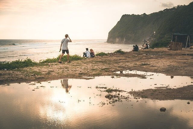 People standing on Canggu beach in Bali Indonesia. Sun is glowing and reflecting in a pool of water in the sand. Four people are looking at the ocean from the sand. Cliff is in the background.