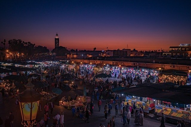 Marrakech morocco at night. Picture is off the Marrakech Medina while the sun is setting. Many markets shown with hundreds of people walking. Sky is dark blue and red.