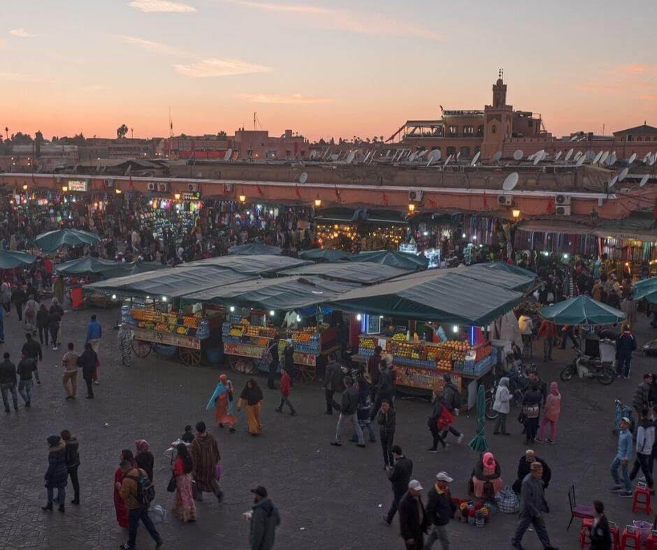 Market in Medina in Marrakech morocco. 20 people walking in Market. Sun is setting at dusk. Three tents that sell street food. Moroccan Scams take place here.