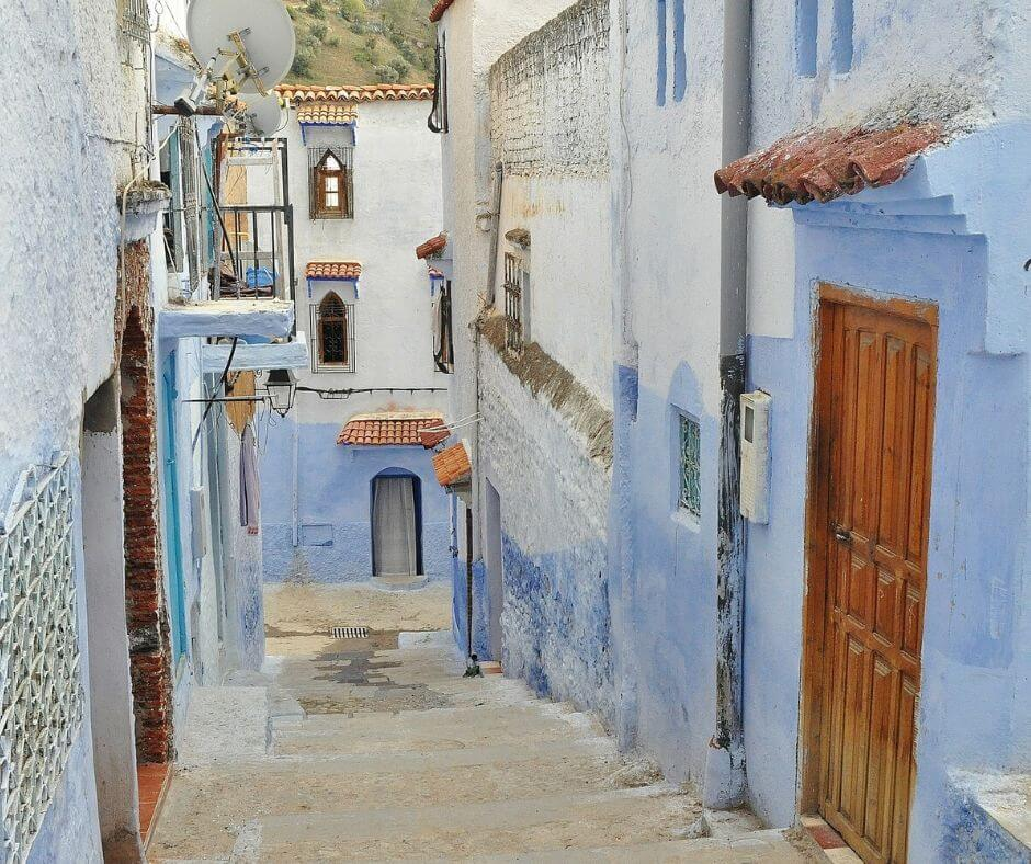 Street where moroccan scams take place displayed. Alleyway in Morocco shown. Blue and white homes line the alleyway in Morocco.