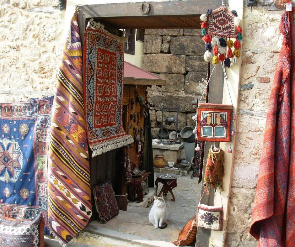 Moroccan scam displayed. Entrance to moroccan carpet shop. Carpets hanging and a cat in doorway.