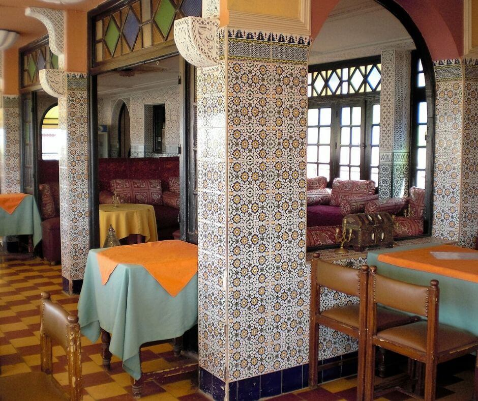 Local moroccan restaurant shown to display a place where Moroccan scams take place. There are three columns with intricate moroccan designs displayed. There are two tables and chairs with blue and orange moroccan cloth.