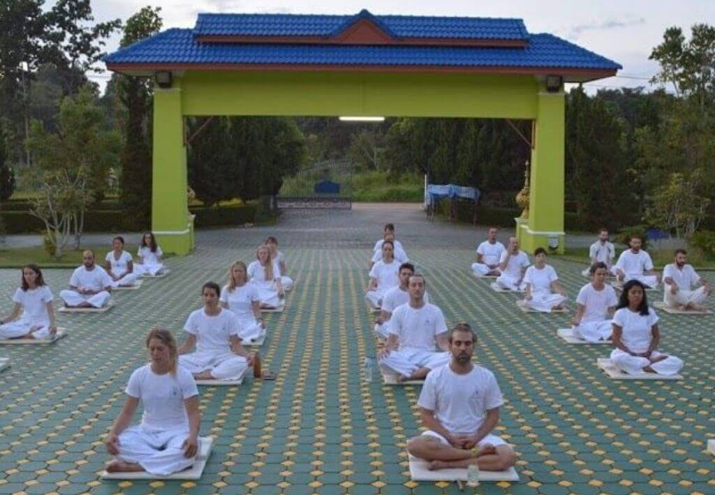 Group of 20 people that are wearing white and meditating while participating in silent meditation retreat in Thailand.