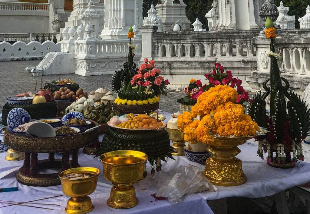 Offerings in front of Wat Suan Dok temple in Thailand. Offerings are flowers that are the colors orange, pink and green. Gold chalices are also in front of the temple.