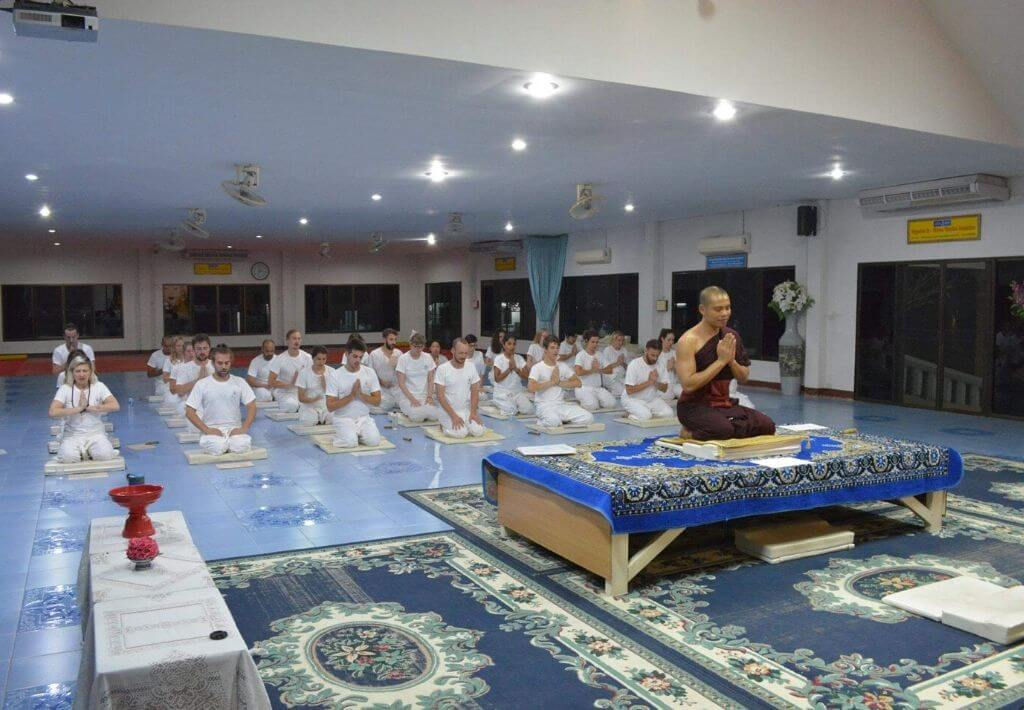 Twenty people kneeling inside a silent meditation retreat in Thailand. The people are kneeling in front of a Buddhist Monk who is wearing dark red robes and leading the silent meditation retreat in Thailand. The retreat is at Wat Suan Dok temple.