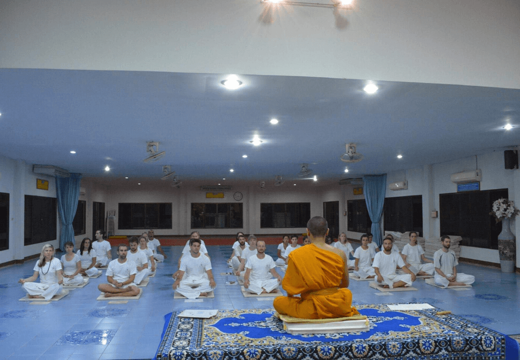 Twenty people wearing white and sitting down in front of a buddhist monk who is wearing orange in front of a Buddhist monk. The people are at Wat Suan Dok