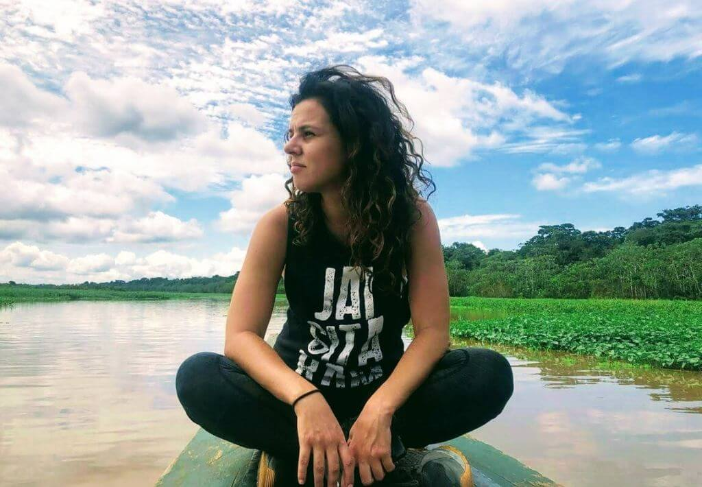 Girl wearing black and white tank top, sitting on top of a wooden boat while floating down the Peruvian Amazon River. Green grass and trees in the background. The start of an Amazon Adventure.