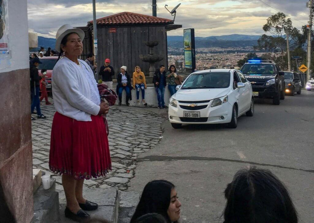 Lady standing in Ecuador with white shirt, hat and red skirt.