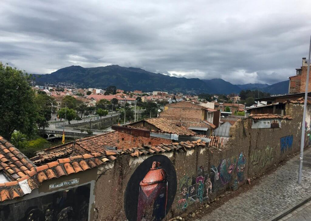 Picture of a fence with graffiti in Cuenca Ecuador. Andes Mountains are in background as well as some homes and other buildings in Cuenca.
