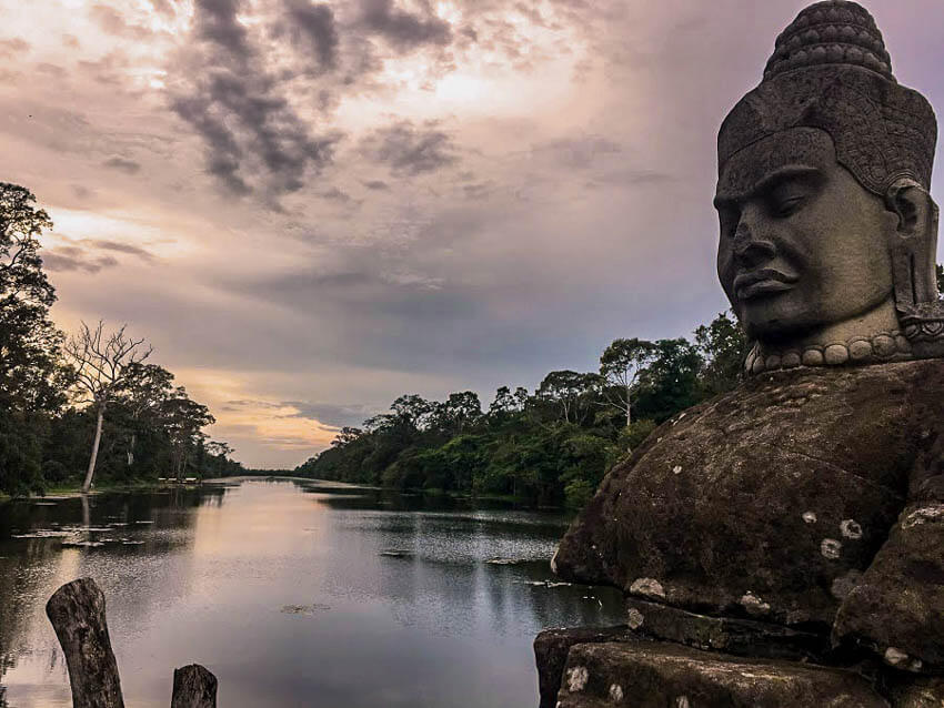 Siem Reap Cambodia - picture of an ancient statue on the side of the road in front of a river