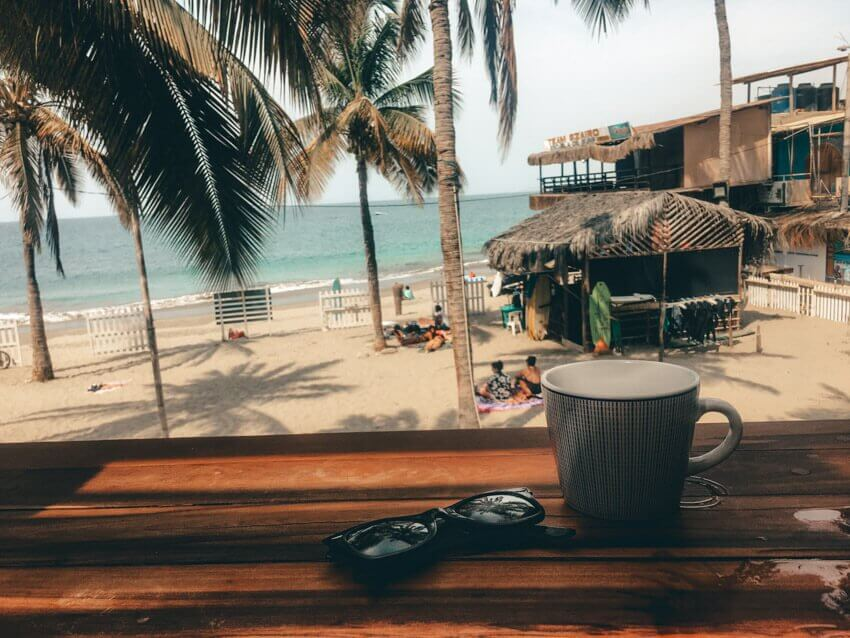 Picture from a restaurant in Playa Mancora with a view of a beach and palm trees. Shows sunglasses and a coffee cup on a table.