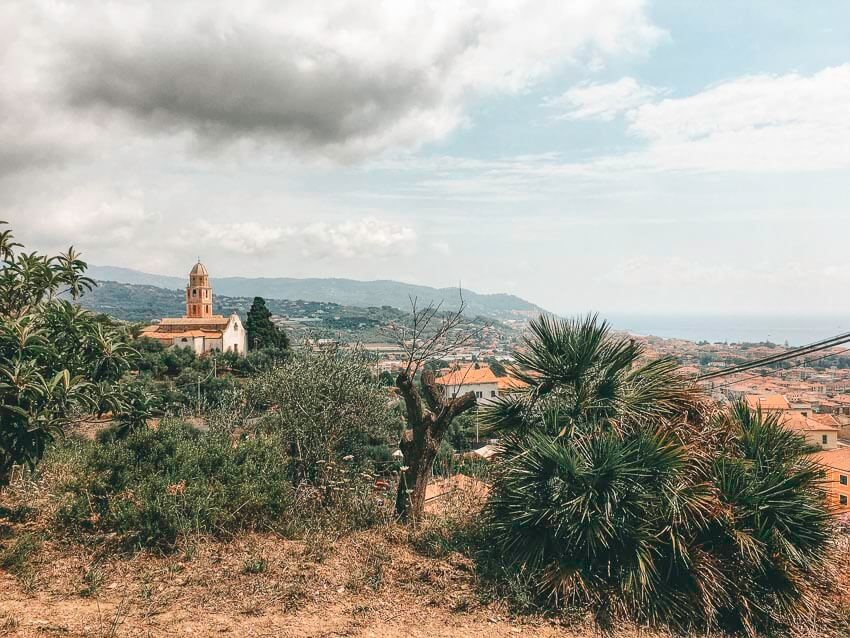 Picture of a town in Diano Marina, Italy. Picture shows trees, bushes, grass and a church in the distance.
