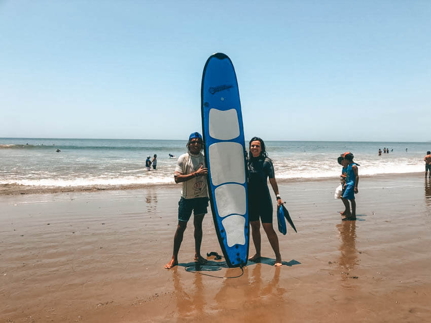 Girl standing with surfboard on beach in Mancora in Peru next to surf instructor