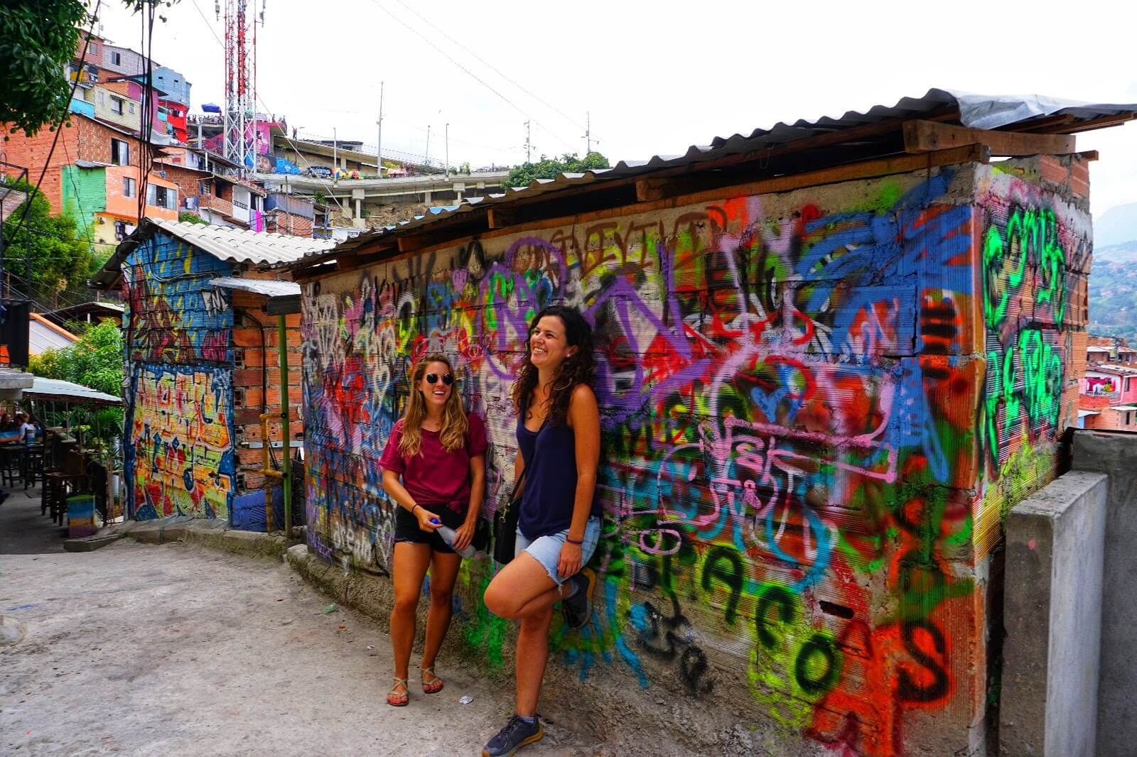 Two girls standing against a wall with colorful street art in Comuna 13, Medellin, Colombia