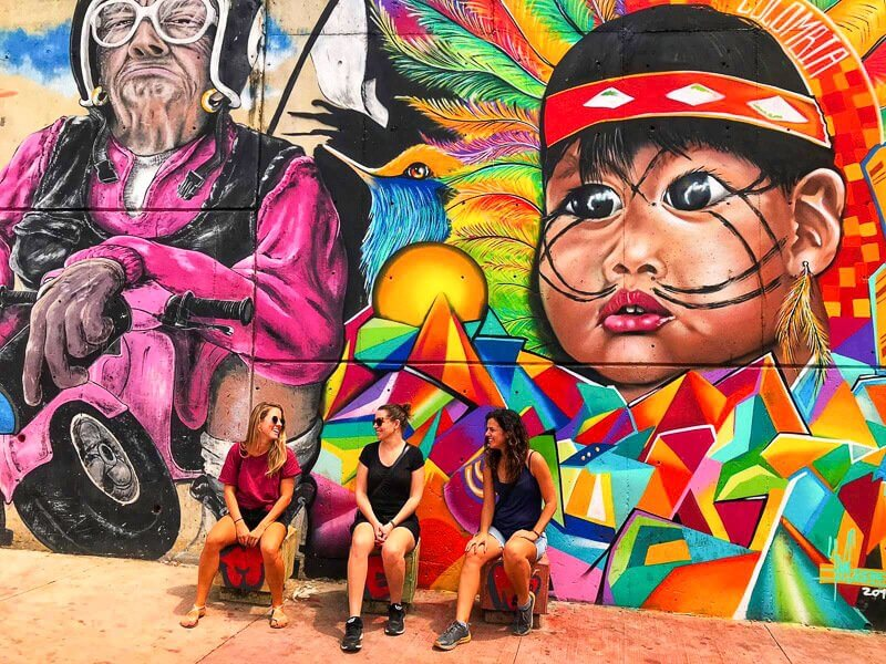 Girls in Comuna 13, sitting in front of vibrant street art