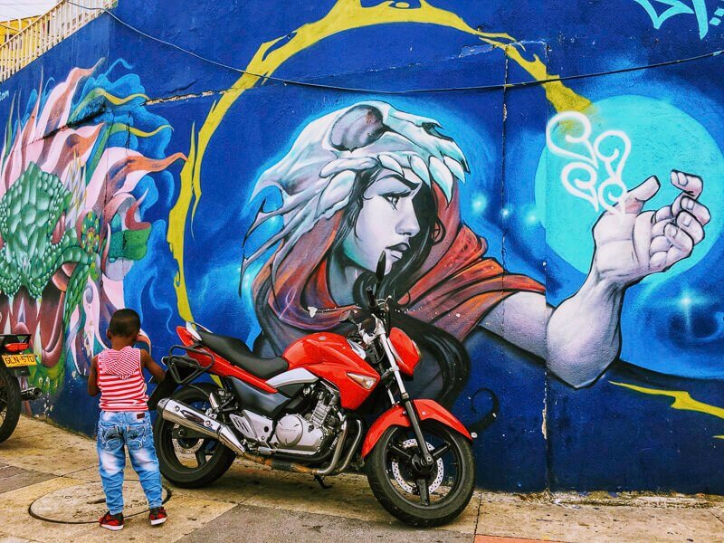 Little boy wearing jeans and a red and white striped t-shirt, standing in front of a motorcycle and a wall with graffiti in Comuna 13