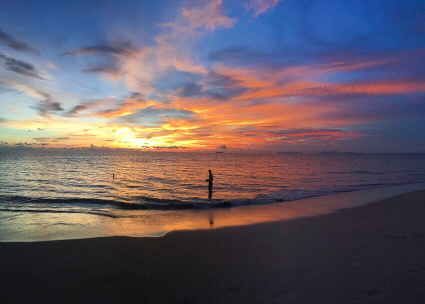 Sunset in Kolanda beach in Thailand. Colors of the sky are blue, orange, yellow and a purplish. There is a man standing in the water looking at the sunset.