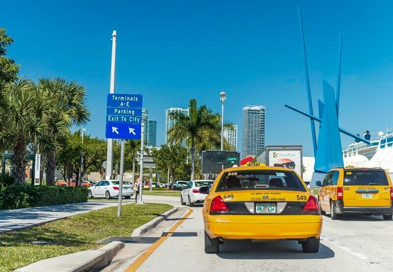 Picture of two yellow taxis driving down a road in Miami.