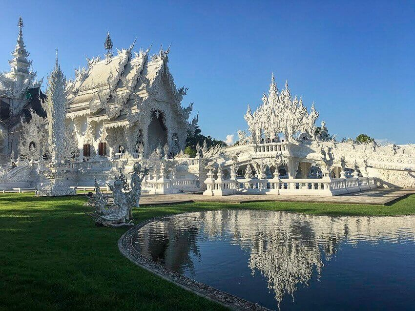 The white temple in Chiang Rai, Thailand. Picture of the white temple in front of a pond.