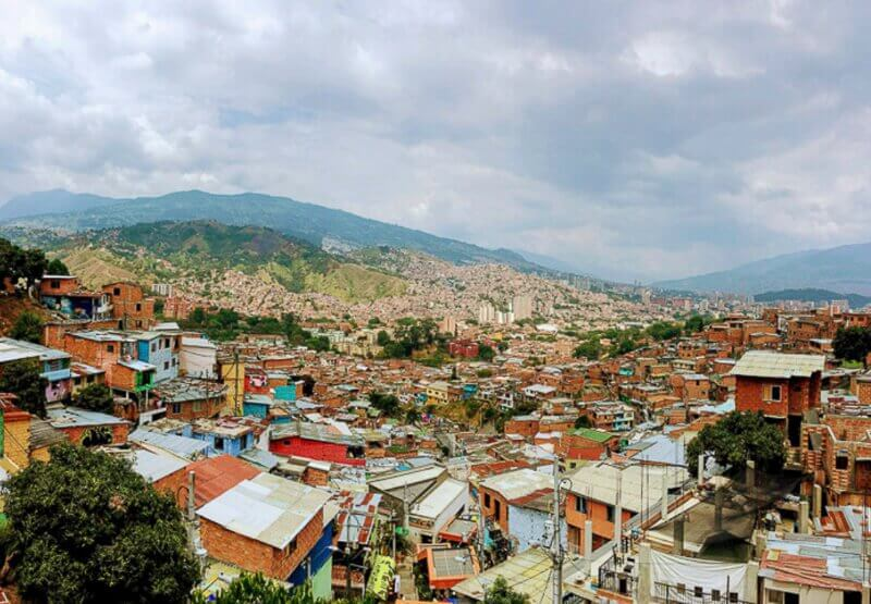 Picture of Comuna 13 in Medellin, Colombia from above. Lots of homes in the neighborhood, trees, and mountains in the distance.