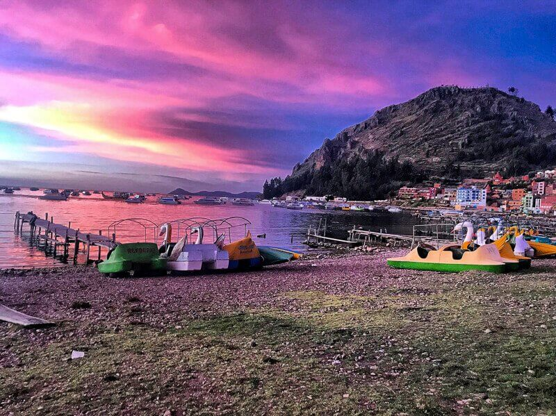Picture of Copacabana, Bolivia at sunset. There is a sky that is multi-colored full of blue, purple, pink and yellow. There is a lake and a mountain as well as a few boats near the lake.