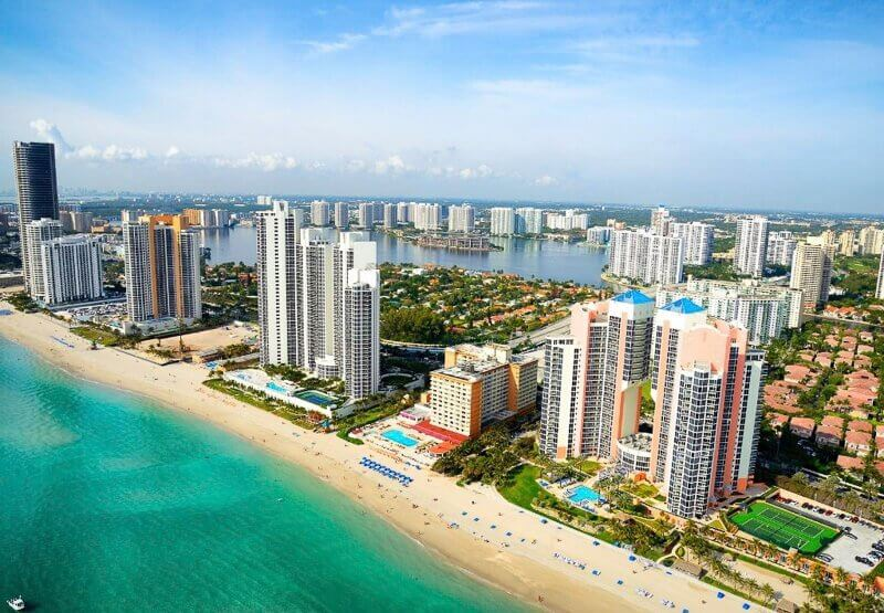 Miami Beach. Picture of hotels with white sand beach and blue water in front.