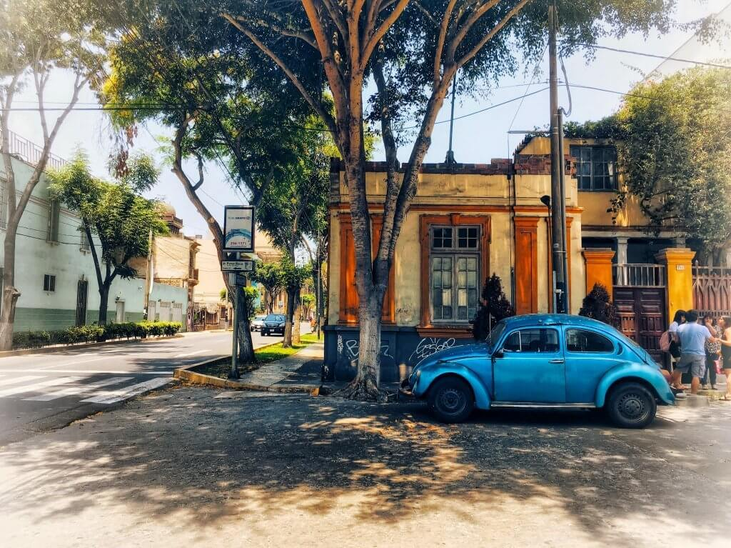 Picture of a yellow and orange house, trees, and a blue buggy car in Barranco, Lima, Peru
