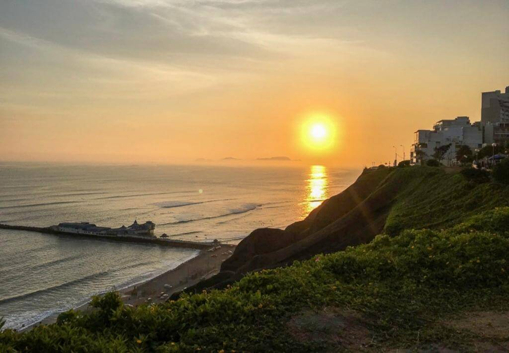 Miraflores, Lima, Peru. Picture of sunsetting over the ocean. Cliff in front of picture and buildings on far right of picture.