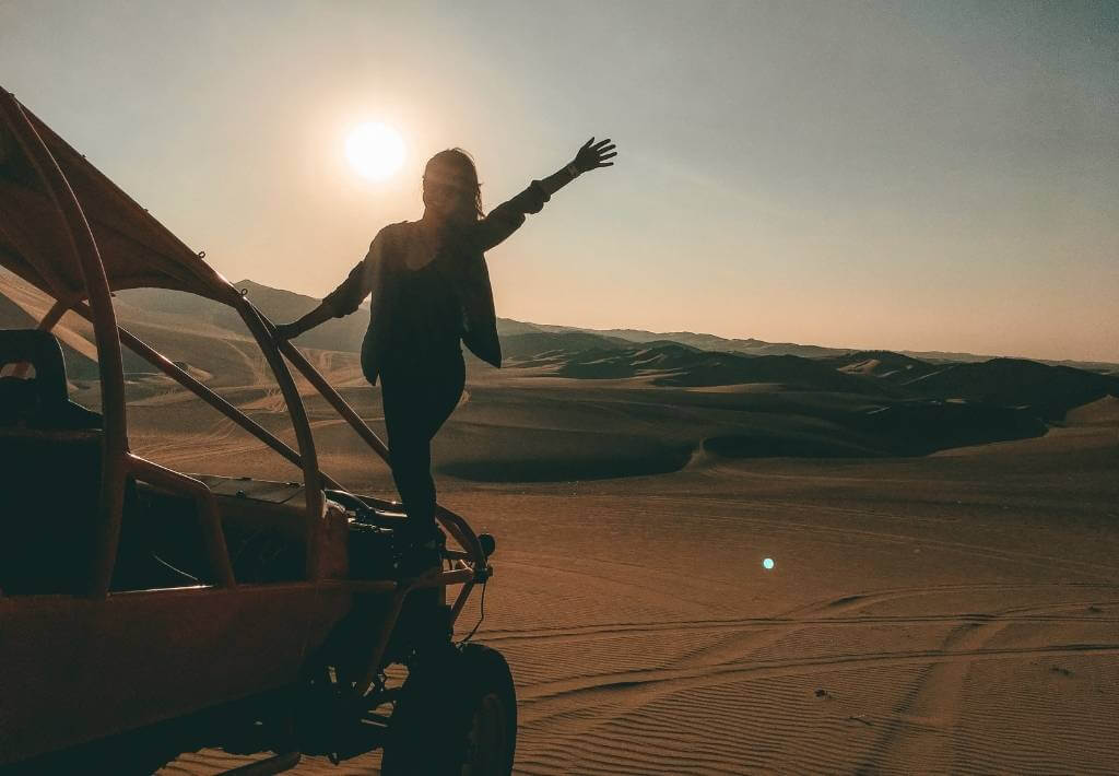 Jagsetter travel blogger on top of a dunebuggy in the middle of the huacachina desert
