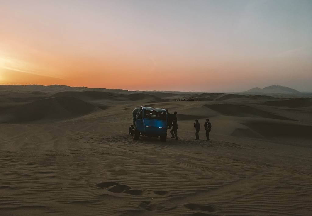 Sand buggy parked in Huacachina desert oasis while sun is setting. 3 people are in front of the car.