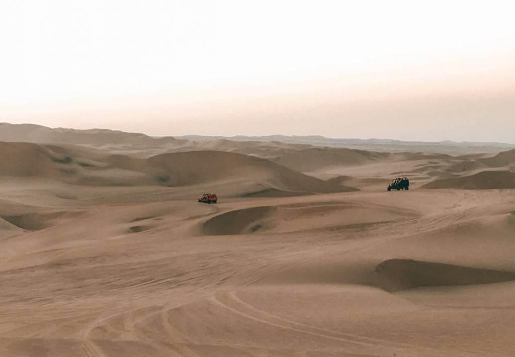 Two sandbuggies driving through huacachina desert oasis