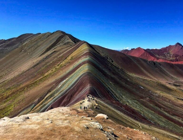 View from the top of the Rainbow Mountain Peak. Blue sky and a mountain of seven colors underneath. There are people walking up the hikes incline.