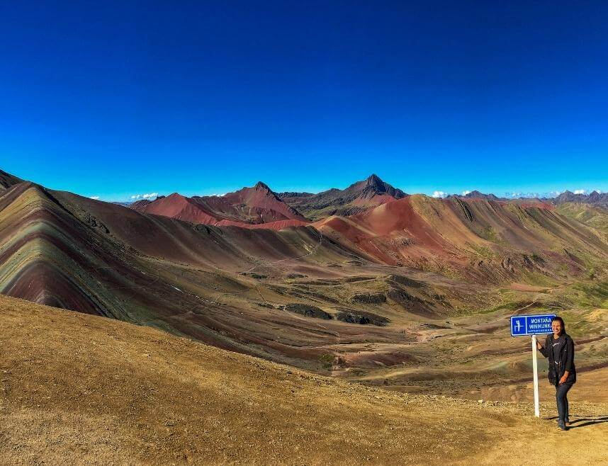 Girl on top of Rainbow Mountain in Peru next to a sign that details its altitude