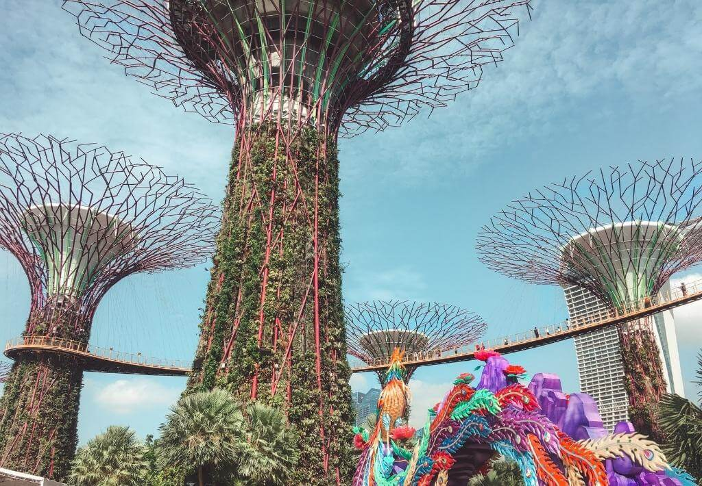 Gardens by the bay. The picture is of large man-made plant structures during the daytime and a colorful man made dragon below it.