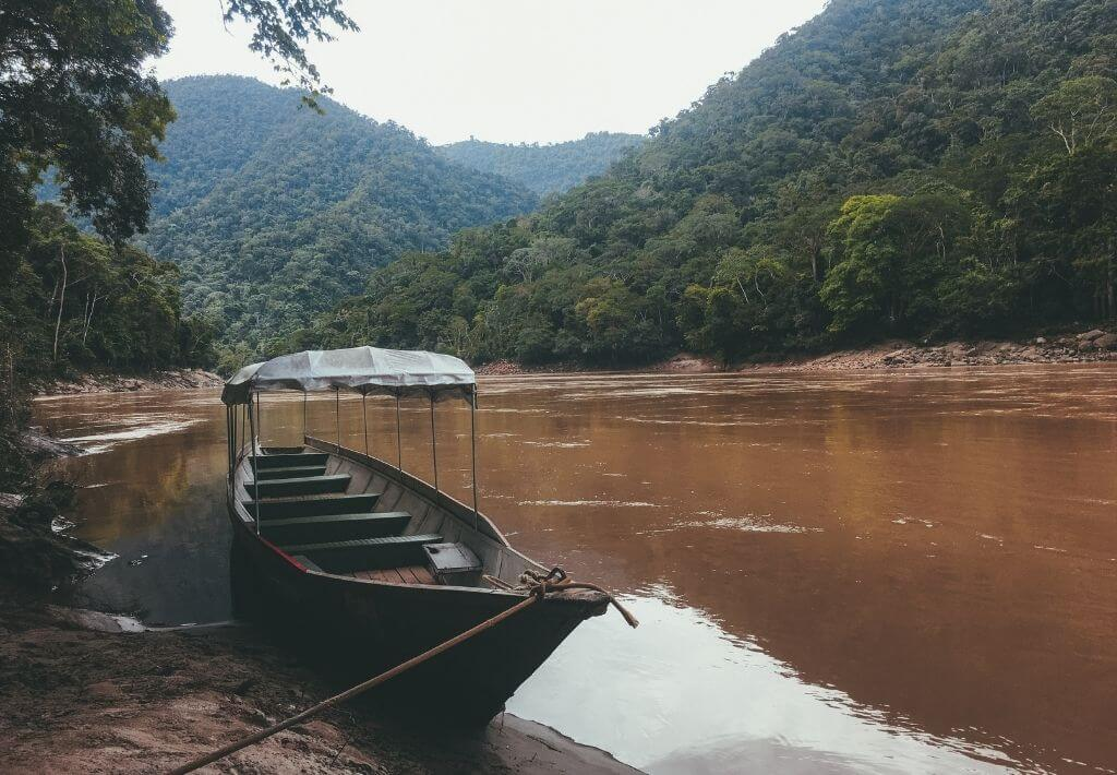 Tarapoto Peru: Picture in a blog post about Peru Itineraries. This picture is of the river in the Amazon and a wooden boat, surrounded by trees