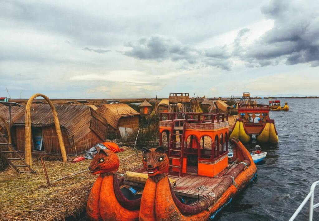 Uros floating islands in Puno, Peru. Picture of a floating island made of straw and a Peruvian boat. Located on Lake Titicaca.