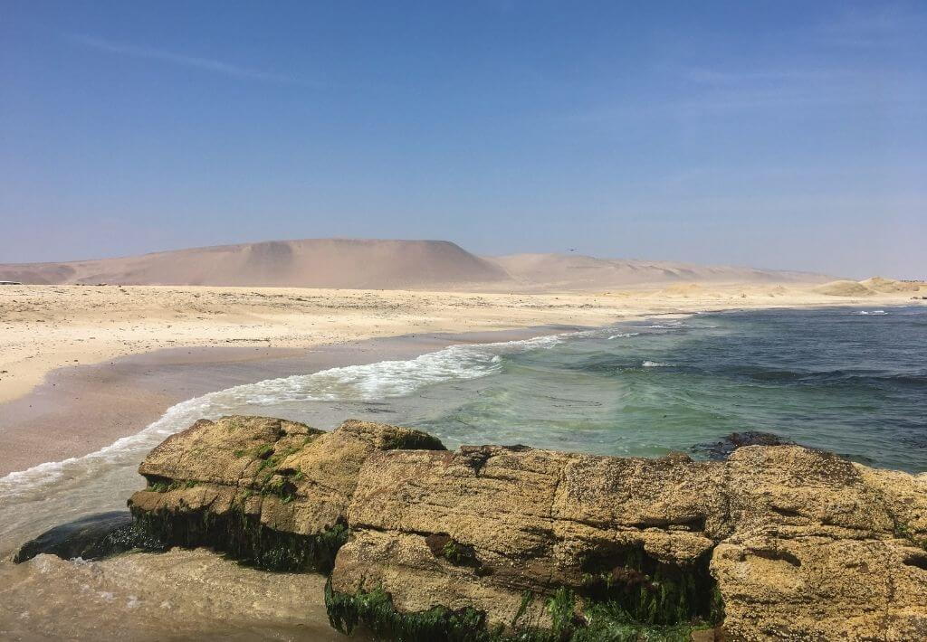 Paracas beach. Picture is of rock formations in front of the ocean and the desert in the background.