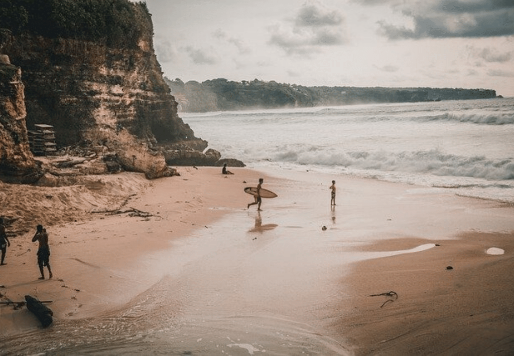 Two surfers entering ocean entering ocean in Indonesia. One man watching them run into the water.