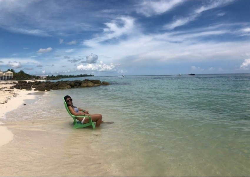 Girl on Grand Bahama Island. Sitting on chair on sand, in front of blue sea.